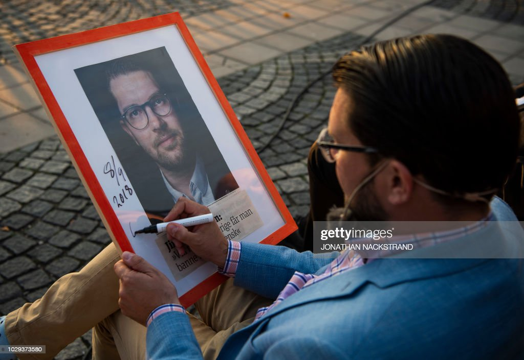 Sweden Democrats party leader Jimmie Akesson signs a framed picture of him before a campaign meeting in Stockholm, Sweden September 8, 2018.