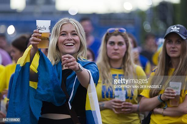 A Sweden fan smiles with a beer as she watches the Euro 2016 group E football match between Sweden and Belgium on a giant screen at the fanzone near...