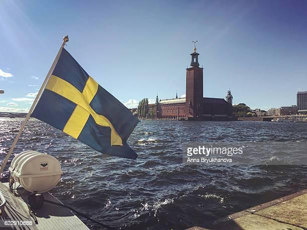 Sweden flag on boat in front of Stockholm City Hall