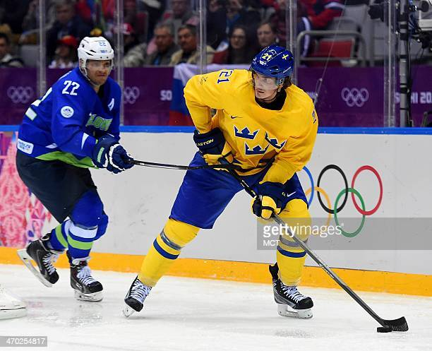 Sweden forward Erica Uden Johansson clears the puck away from Slovenia forward Marcel Rodman during the first period in a men's hockey quarterfinals...