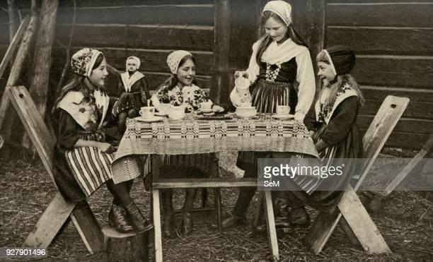 Sweden. Four merry little maids of Leksand are enjoying an open-air tea-party. 1920.