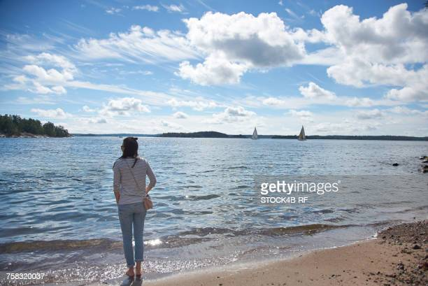 """""""sweden, grinda island, woman on the beach"""" - rolled up pants stock pictures, royalty-free photos & images"""
