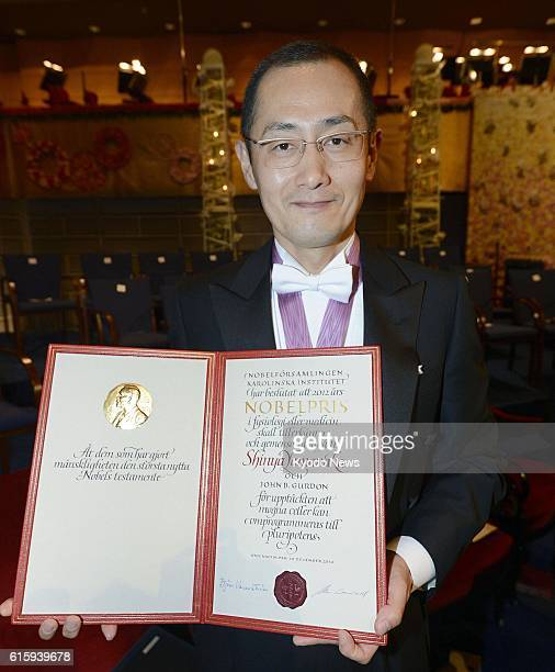 STOCKHOLM Sweden Japanese stem cell researcher Shinya Yamanaka a corecipient of the 2012 Nobel Prize in medicine shows his Nobel Prize diploma after...