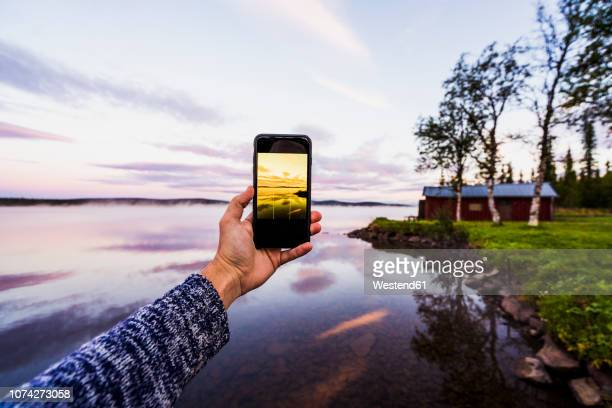 sweden, lapland,  person taking a smartphone picture of the sunset - swedish lapland stock-fotos und bilder