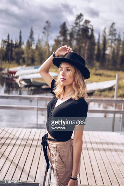 sweden, lapland, portrait of fashionable blond woman wearing black hat standing on jetty - norrbotten province stock pictures, royalty-free photos & images