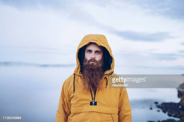 sweden, lapland, portrait of serious man with full beard wearing yellow windbreaker - vollbart stock-fotos und bilder