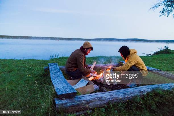 Sweden, Lapland, Two friends preparing a bonfire at the lakeshore