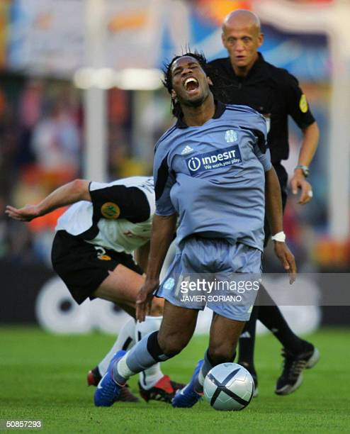 Marseille's Ivorian forward Didier Drogba is tackled by Valencia's Carlos Marchena during the final of the UEFA cup football match at the Ullevi...
