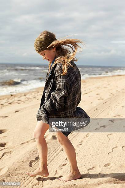 Sweden, Mellby, girl with blowing hair walking on the wearing her fathers shirt