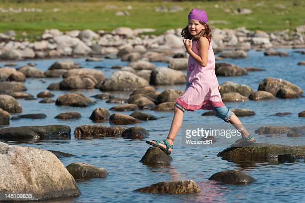 Sweden, Molle, Girl balancing on rock in water