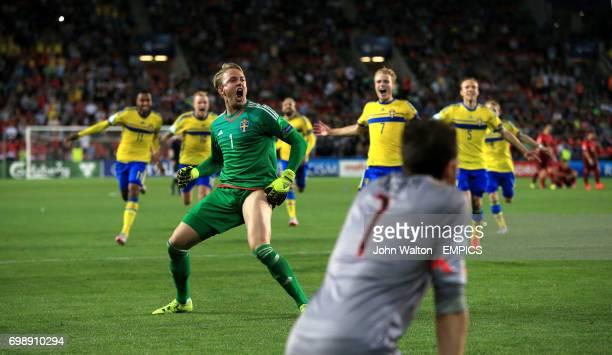 Sweden players including Patrik Carlgren celebrate winning the penalty shootout as Portugal goalkeeper Jose Sa kneels dejected
