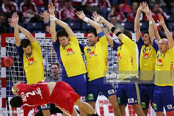 Sweden players try to block shot by Bartlomiej Jaszka of Poland during the Men's European Handball Championship 2012 group 1 match between Poland and...