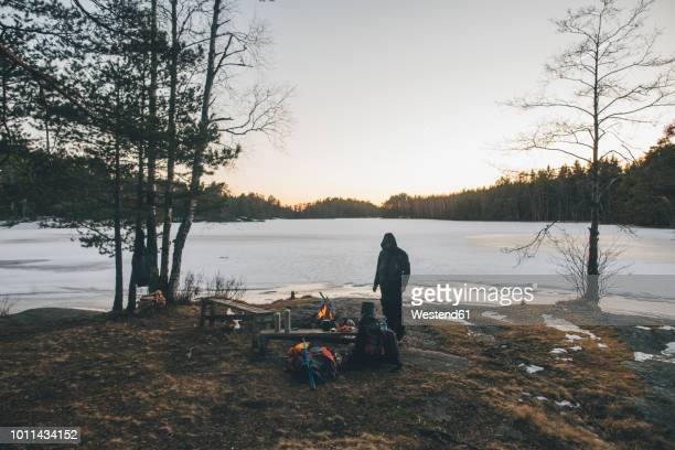 sweden, sodermanland, backpacker resting at a remote lake in winter - simple living stock pictures, royalty-free photos & images