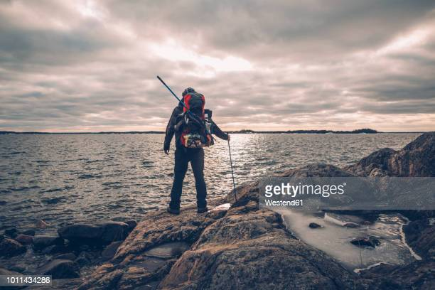 Sweden, Sodermanland, backpacker standing at the seashore under cloudy sky