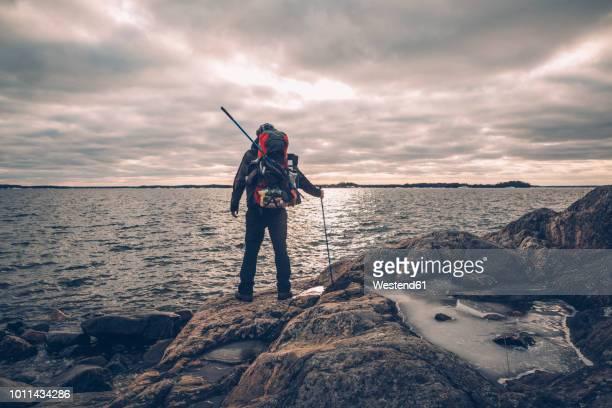 sweden, sodermanland, backpacker standing at the seashore under cloudy sky - wasserrand stock-fotos und bilder