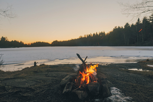 Sweden, Sodermanland, campfire at lakeside in winter - gettyimageskorea