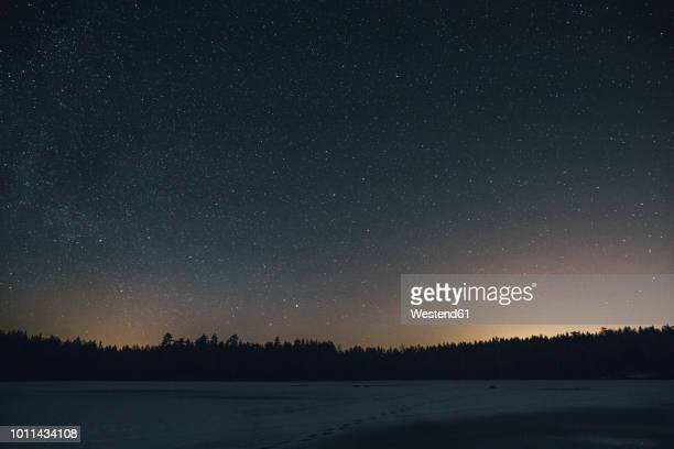 sweden, sodermanland, frozen lake navsjon in winter under starry sky at night - night stockfoto's en -beelden