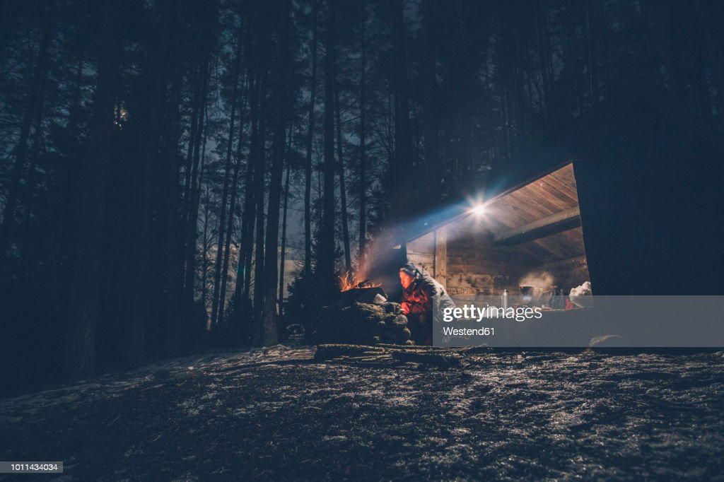 Sweden, Sodermanland, man at shelter with campfire at night : Stock-Foto