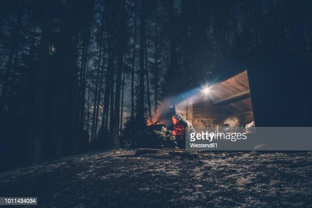 sweden, sodermanland, man at shelter with campfire at night - hut stock pictures, royalty-free photos & images