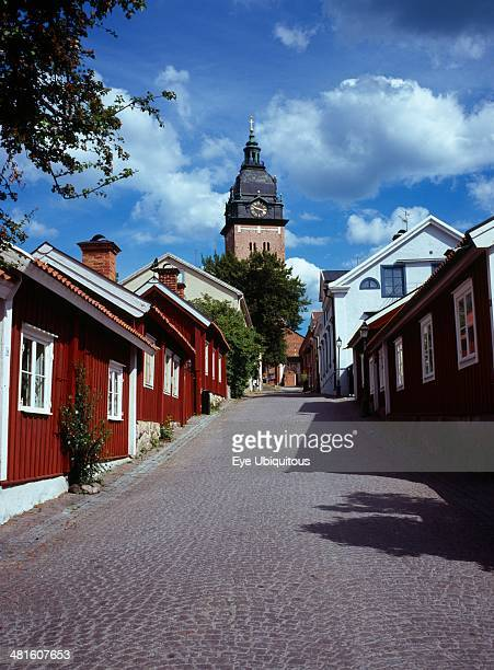 Sweden Sodermanland Strangnas Cobbled street lined by wooden houses leading to Domkyrkan Cathedral