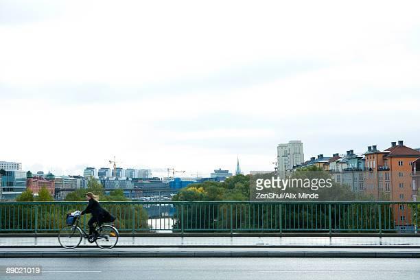 sweden, stockholm, bicyclist riding across bridge - 中距離 ストックフォトと画像