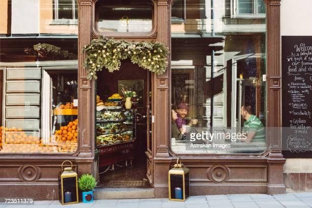 sweden, stockholm, gamla stan, friends having coffee, seen through coffee shop window - stockholm stock-fotos und bilder