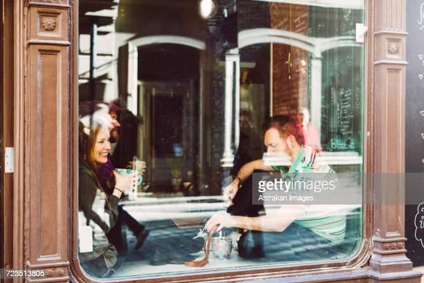 Sweden, Stockholm, Gamla Stan, Friends having coffee, seen through coffee shop window