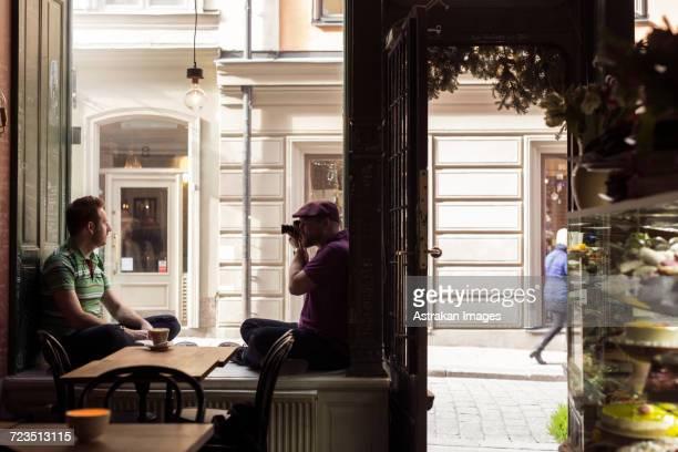 Sweden, Stockholm, Gamla Stan, Man photographing friend in coffee shop