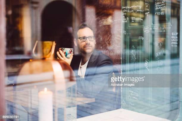 Sweden, Stockholm, Gamla Stan, Man relaxing in cafe seen through window