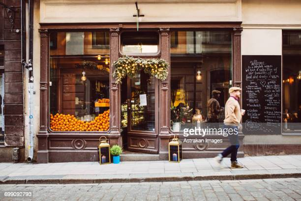 sweden, stockholm, gamla stan, man walking by cafe - stockholm stock pictures, royalty-free photos & images