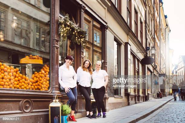 Sweden, Stockholm, Gamla Stan, Portrait of three female cafe workers standing outdoors