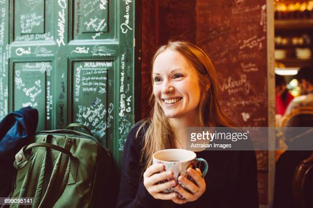 Sweden, Stockholm, Gamla Stan, Smiling woman holding coffee cup in cafe