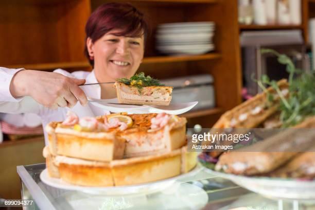 Sweden, Stockholm, Gamla Stan, Smiling woman serving tart in cafe