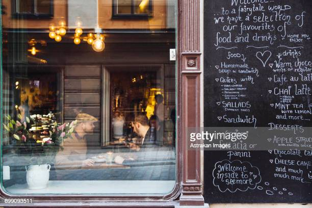 Sweden, Stockholm, Gamla Stan, Two men having coffee, seen through coffee shop window
