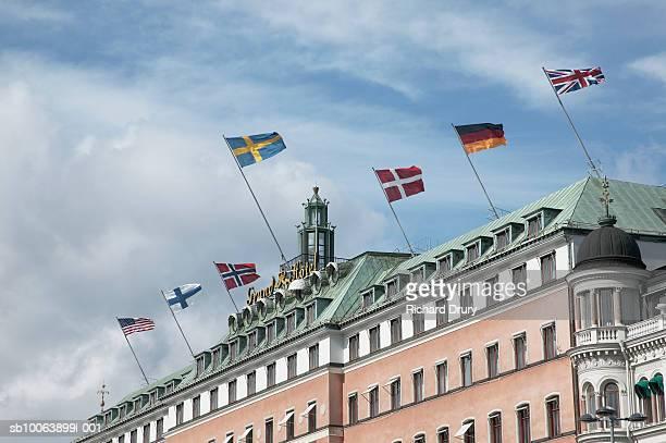 sweden, stockholm, row of flags on top of grand hotel - ストックホルム グランドホテル ストックフォトと画像
