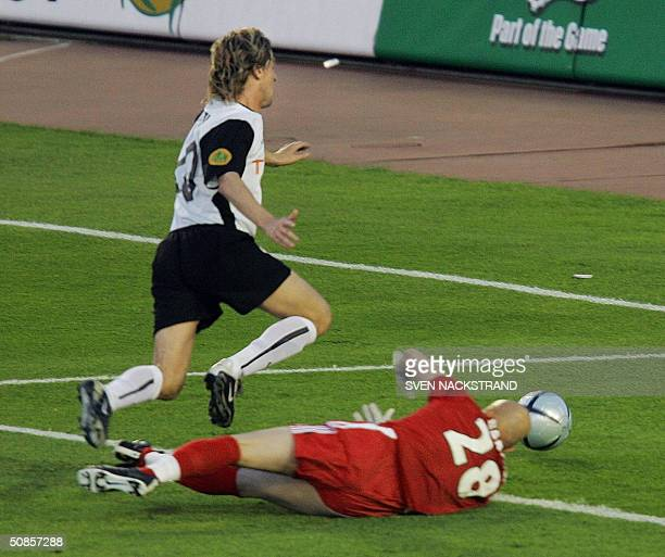 Valencia's Spanish forward Mista is taken down by Marseille's French goalkeeper Fabien Barthez to earn Valencia a penalty during the final of the...