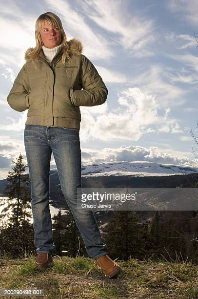 sweden, young woman with hands in pockets, mountains in background - fur trim stock pictures, royalty-free photos & images