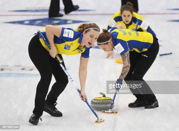 Sweden's Agnes Knochenhauer and Sofia Mabergs clear a path for the stone as Anna Hasselborg looks on during the semifinal Russia vs Sweden at the...