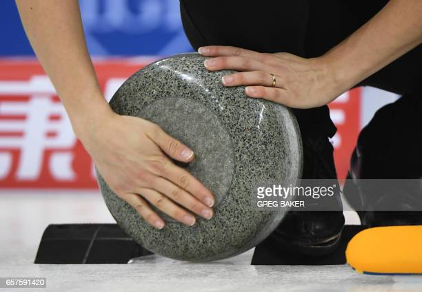 Sweden's Agnes Knochenhauer cleans the stone during their playoff against Scotland at the Women's Curling World Championships in Beijing on March 25...