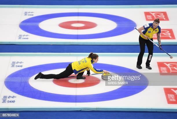 Sweden's Anna Hasselborg releases the stone as teammate Sofia Mabergs looks on during their playoff against Scotland at the Women's Curling World...