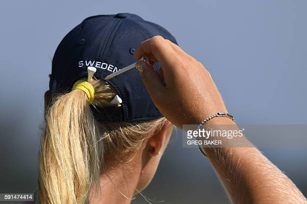 Sweden's Anna Nordqvist pulls out a tee from her pony tail during the Women's individual stroke play at the Olympic Golf course during the Rio 2016...