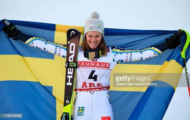 Sweden's Anna Swenn Larsson celebrates with her national flag after placing second in the women's slalom event at the 2019 FIS Alpine Ski World...