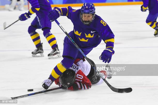 TOPSHOT Sweden's Annie Svedin falls over Japan's Haruna Yoneyama in the women's classifications ice hockey match between Sweden and Japan during the...