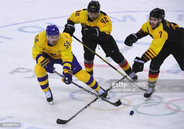 TOPSHOT Sweden's Anton Lander and Germany's Daryl Boyle fight for the puck as Germany's Yasin Ehliz looks on in the men's quarterfinal ice hockey...