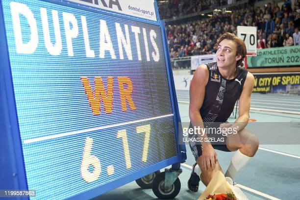 Sweden's Armand Duplantis celebrates next to the board after he broke world pole vault record of 6.17 metres at the Orlen Copernicus Cup 2020 World...