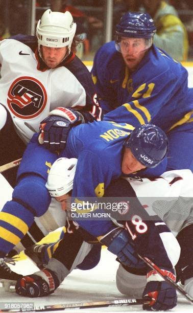 Sweden's Calle Johansson falls on Adam Deadmarsh of the US as Swede Peter Forsberg and Anthony Amonte of the US look on during their men's lympic...