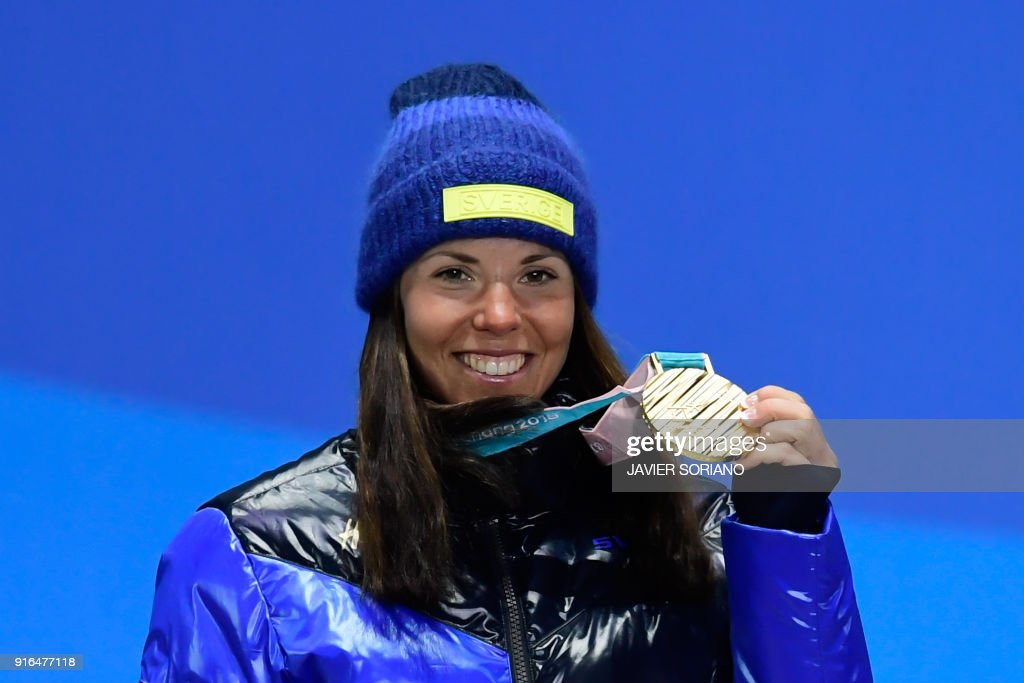 TOPSHOT - Sweden's Charlotte Kalla celebrates on the podium during the medal ceremony after taking first place in the women's 7.5km + 7.5km cross-country skiathlon event at the Pyeongchang Medals Plaza during the Pyeongchang 2018 Winter Olympic Games on February 10, 2018 in Pyeongchang. /