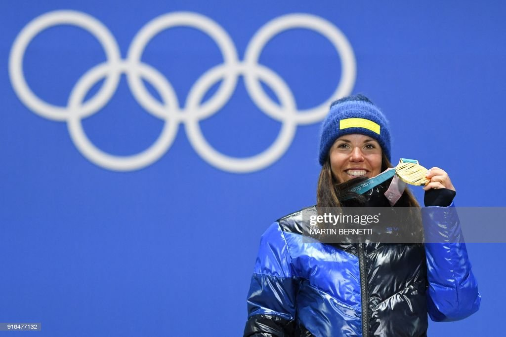 Sweden's Charlotte Kalla celebrates on the podium during the medal ceremony after taking first place in the women's 7.5km + 7.5km cross-country skiathlon event at the Pyeongchang Medals Plaza during the Pyeongchang 2018 Winter Olympic Games on February 10, 2018 in Pyeongchang. / AFP PHOTO / Martin BERNETTI