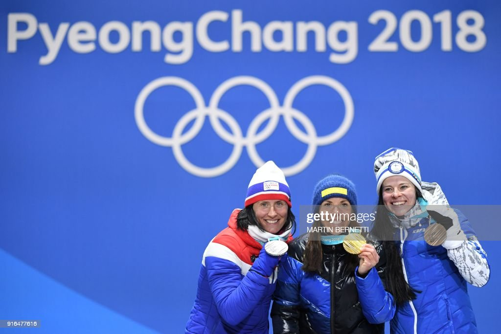 Sweden's Charlotte Kalla (C), Norway's Marit Bjoergen (L) and Finland's Krista Parmakoski celebrate on the podium during the medal ceremony at the end of the women's 7.5km + 7.5km cross-country skiathlon event at the Pyeongchang Medals Plaza during the Pyeongchang 2018 Winter Olympic Games on February 10, 2018 in Pyeongchang. / AFP PHOTO / Martin BERNETTI