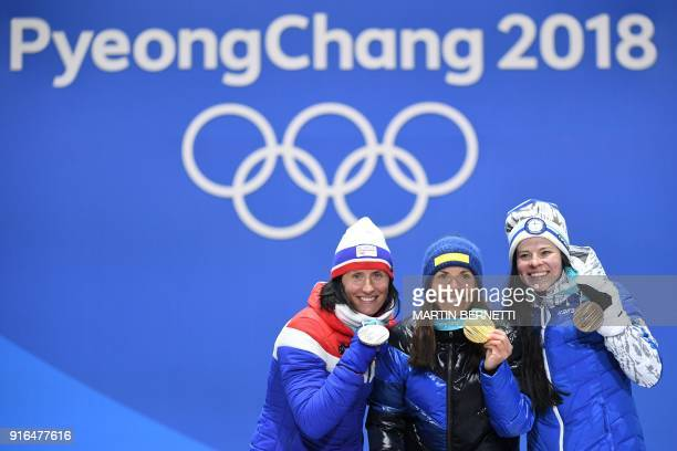 Sweden's Charlotte Kalla Norway's Marit Bjoergen and Finland's Krista Parmakoski celebrate on the podium during the medal ceremony at the end of the...